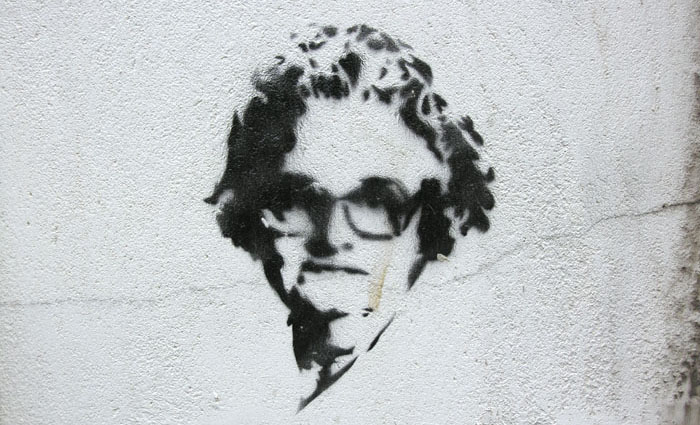 A black stenciled image of an older woman applied to a white wall | All rights reserved by the image creator: Maarten Idema. Copyright 2006.